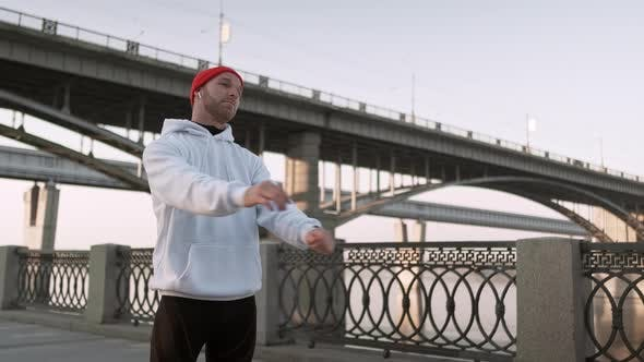 Thumbnail for Young Man Stretching His Arm Muscles Under the Bridge Before Running. Handsome Athlete Male Doing