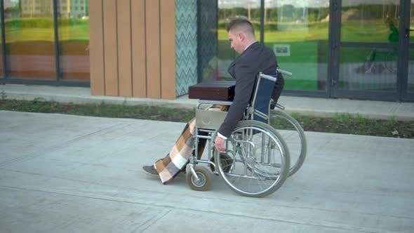 Thumbnail for Young Businessman in a Suit in a Wheelchair. A Serious Man Is Riding in a Wheelchair Against a