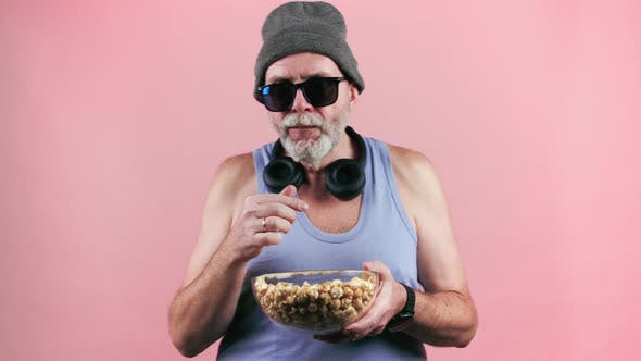 Thumbnail for Footage of aged man in tank top and hat with popcorn.