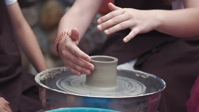 Grandmother with a Grandchildren Make Pitchers in Pottery