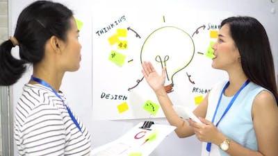 Positive Asian Businesswoman Doing Presentation for Colleague