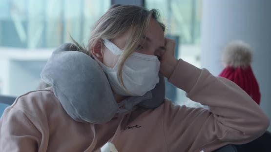 Bored Woman in Mask with Travel Pillow Waits for Flight