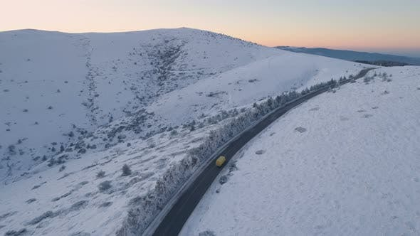 Drone Follows Yellow Van on Beautiful Snowy Mountain Road with Sunset Sky