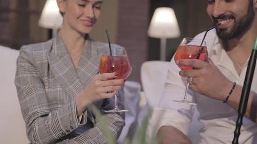Hookah Bar. Couple Drinking Cocktails And Smoking Fruit Shisha