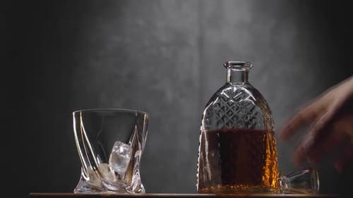 Whiskey Glass and Bottle on Table Against Dark Gray Background