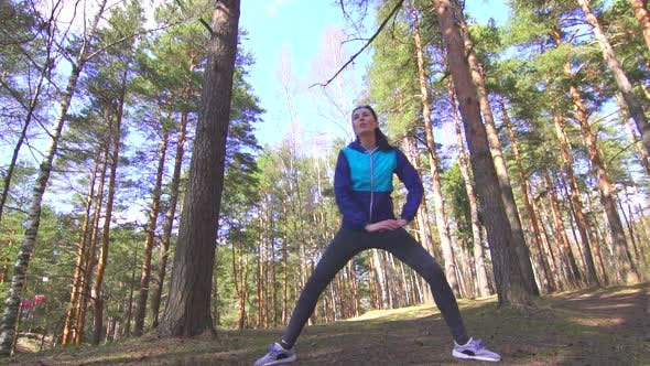 Sports Girl Brunette Stretching in a Sunny Forest