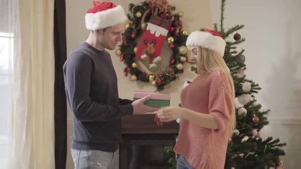 Thumbnail for Young Caucasian Man in New Year Hat Giving Gift Box To Pretty Woman. Cute Girl Opening Present and