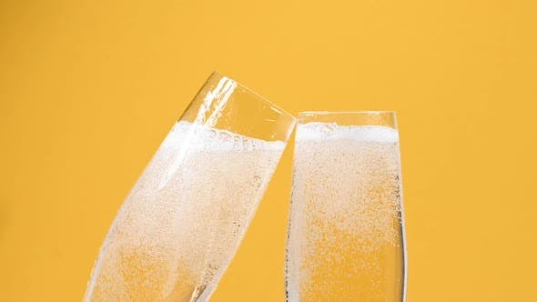 Pouring champagne sparkling white wine in two glasses over vivid yellow background