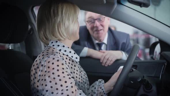 Thumbnail for Side View of Beautiful Mature Caucasian Woman Sitting on Driver's Seat and Talking with Elderly