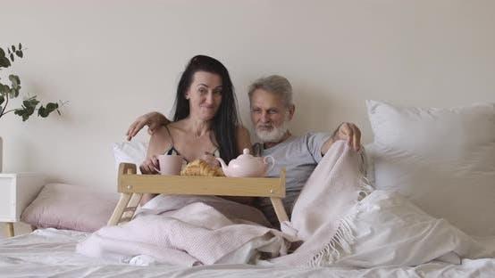Thumbnail for Weitaufnahme Porträt von glücklich Senior Kaukasier Mann und Frau liegend im Schlafzimmer mit Tee und Croissants