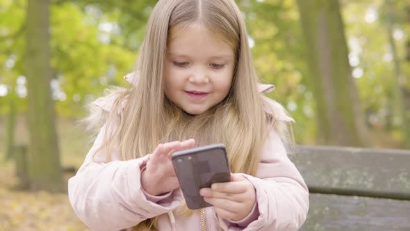 Cute Little Caucasian Girl Plays with a Smartphone and Smiles Then Gets Help From Her Mom