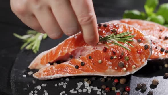 Thumbnail for A Cook Puts a Sprig of Rosemary on a Salmon steak.Raw Salmon Red Fish with Pepper and Salt.