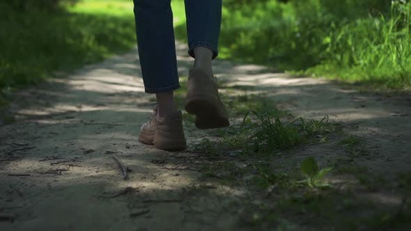 View of Legs of Young Woman Walking on Path in Forest on Summer Day Spbd