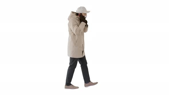 Thumbnail for Man Wears Protective Medical Mask and Talks on the Phone Walking on White Background.