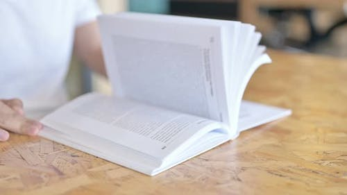 Close Up of Hands Skimming a Book