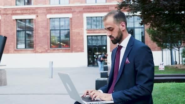 Thumbnail for Young Businessman Working on the Laptop in a Business District, Close Up Slow Motion