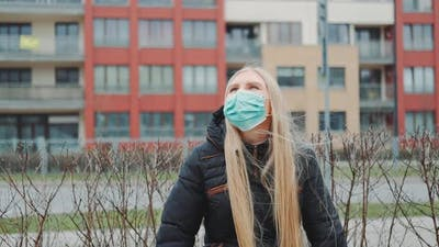 Blonde Girl in a Medical Mask Sitting on the Bench