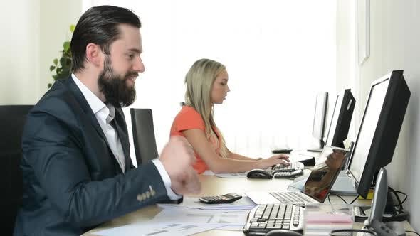 Thumbnail for Woman and Man Work on Desktop Computer and Man Rejoices in the Office (Workers)