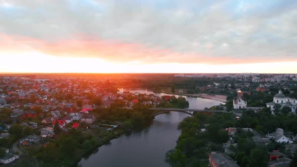 Drone Fly Above River in Beautiful Small European City During Sunset in Spring