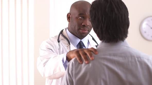 Thumbnail for Over the shoulder shot of doctor talking to Hispanic patient