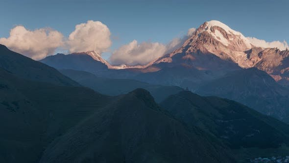 Cover Image for Sunrise in Caucasian Highland. Kazbek Mountain Peak with Snow Cap Glacier in Sun Rays Shadows