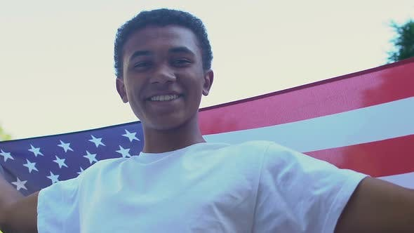 Thumbnail for Afro-American teen boy with US flag smiling at camera outdoors