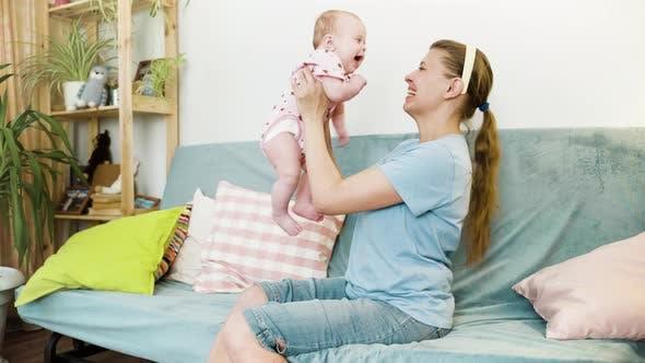 Thumbnail for Mutter Frau mit neugeborenen baby umarmt und mit Spaß in Zimmer
