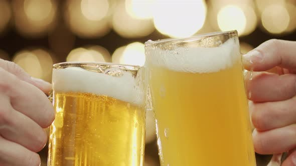 Close-up shot of two hands toast beer spilling beer bokeh background.