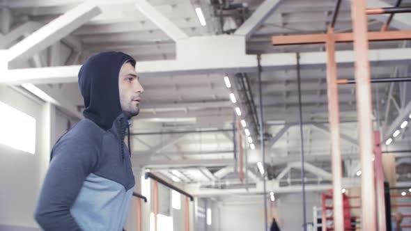 Fitness Man in Sport Hoodie Running Inside Gym Club