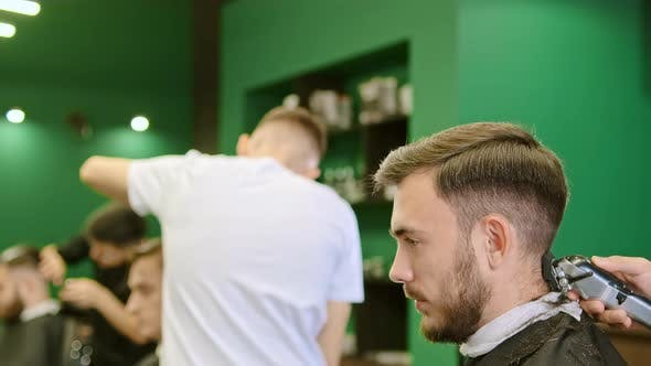 Hand Holds Clipper and Trims Customer Hair in Barbershop