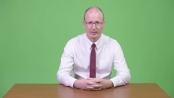 Thumbnail for Mature Bald Businessman Looking Tired While Explaining Something Against Wooden Table