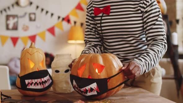 Thumbnail for Black Woman Putting Halloween Face Mask on Jack-o-Lantern