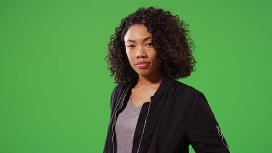 Thumbnail for Portrait of stylish woman looking around in black bomber jacket on greenscreen