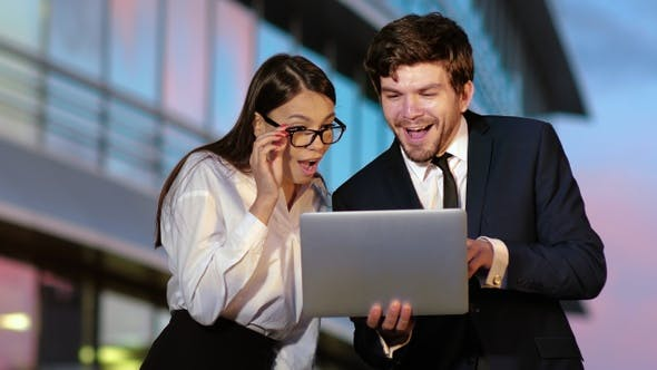 Thumbnail for Excited business couple receiving good news on laptop.