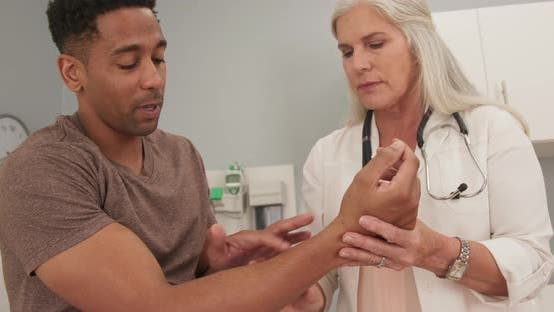 Thumbnail for Close up of african-american male talking to mature doctor about arm injury