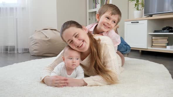 Happy Smiling Children Hugging and Having Fun with Mother on Carpet in Living Room