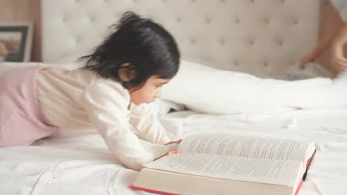 Little Adorable Girl Concentrated on Reading a Book, Little Bookworm