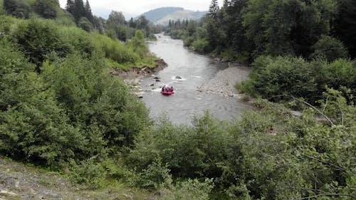 People Kayaking on Rapid River Stream