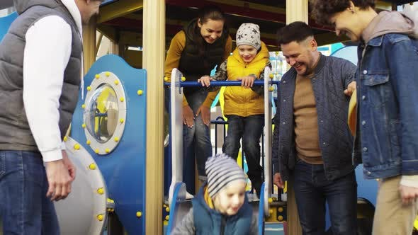 Cheerful Parents Spending Time with Kids on Playground