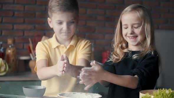 Thumbnail for Boy and Girl Are Cooking and Clapping Their Hands in Flour