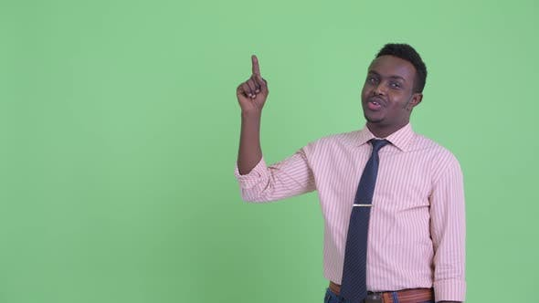 Thumbnail for Happy Young African Businessman Talking While Pointing Up