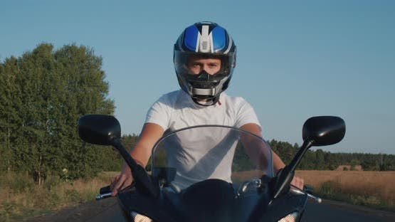 Young Man Rides a Motorcycle on the Highway