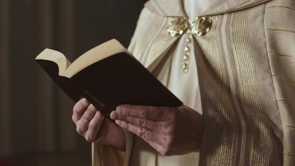 Unrecognizable Priest Reading Holy Bible