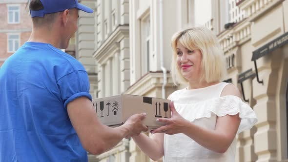 Cover Image for Lovely Woman Receiving Cardboard Box Parcel From a Delivery Man