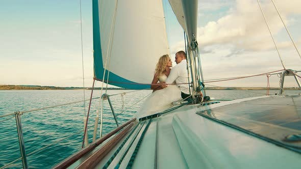 The Newlyweds Are Sailing on the Lake Aboard the Yacht. They Enjoy Each Other, Look and Smile