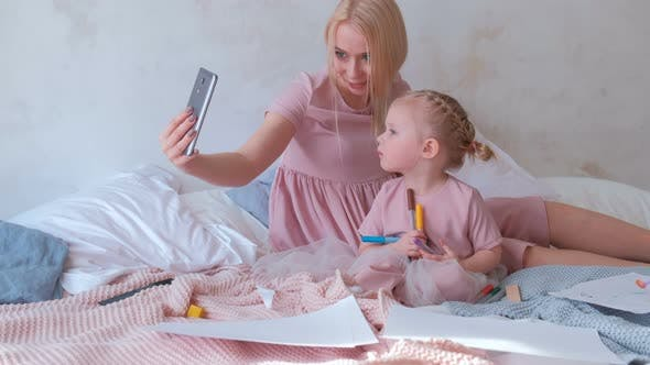 Thumbnail for Young Attractive Blond Mom Take a Photo in Mobile Phone with Her Little Charming Daughter in Pink