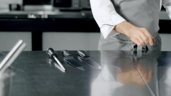 Thumbnail for Chefkoch Vorbereitung auf Kochen in der Küche. Nahaufnahme Mann Hände legen Messer