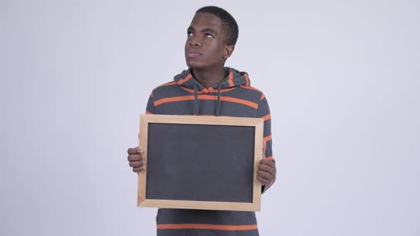 Thumbnail for Young Happy African Man Thinking While Holding Blackboard