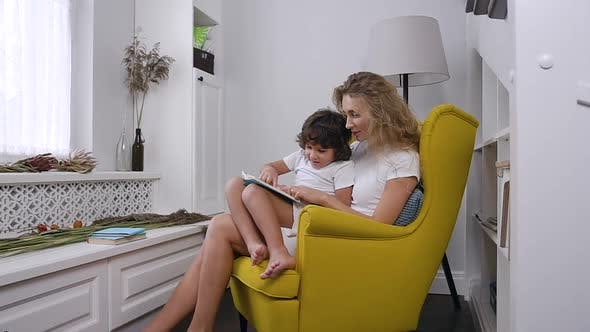 Thumbnail for Mom Reads Child book to her little son while sitting in comfortable yellow armchair