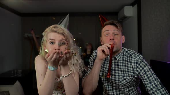Beautiful Young Couple Having Fun at Party Blowing Party Whistles Confetti